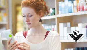 A red-headed woman examining a consumer product. The UL Verification Mark is to the right of the woman and a check mark is to the left of the Verification Mark