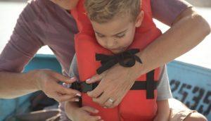 woman putting orange life jacket on young child