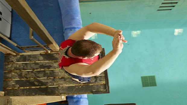 Man standing in dive position (hands up) on platform.