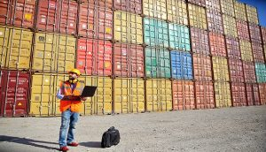 man standing in front of multiple cargo containers