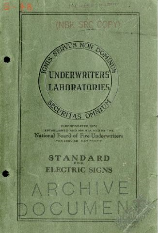 """Aged, green cover from the 1917 published Standard for Electric Signs. UL is spelled out in the center of a black circle with the words"""" ignis servus non dominus securitas omnium""""."""
