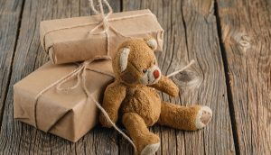 Brown toy bear on a wooden rustic table.