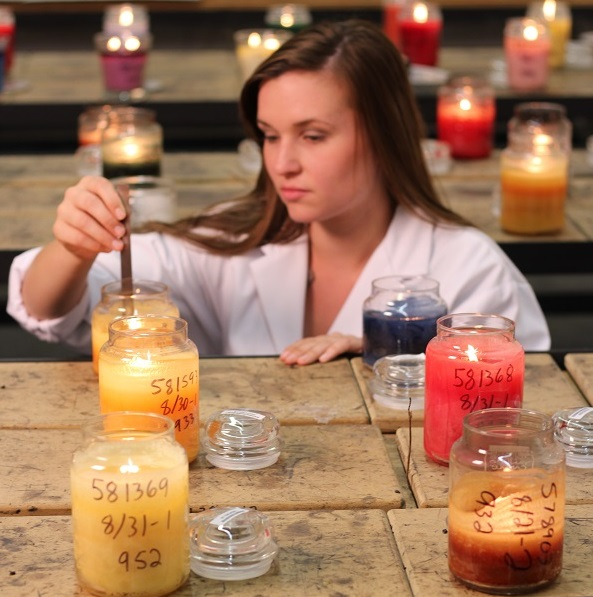 a small ruler measures the height of the wick.