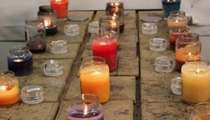 various candles sitting on a wooden plank table