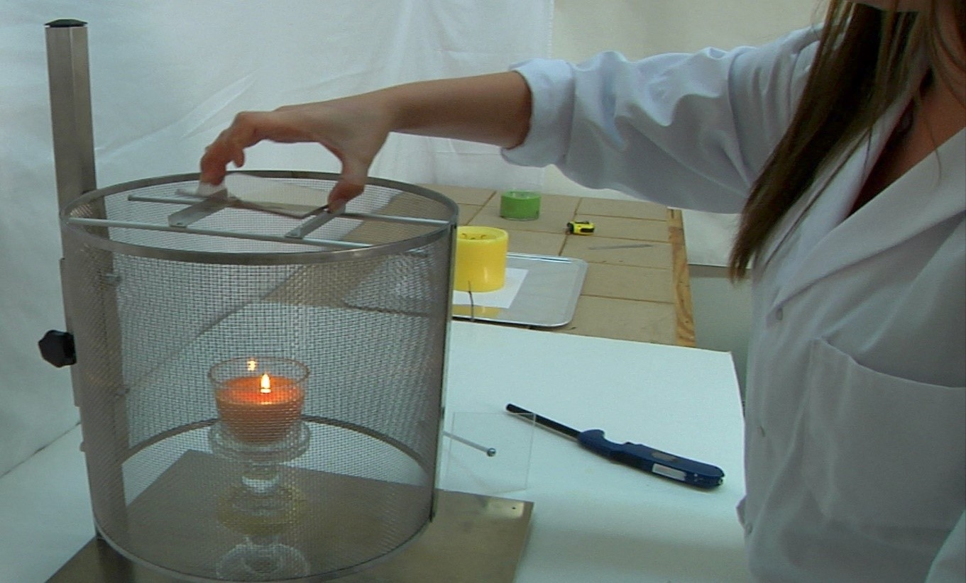candle in glass votive is placed inside what looks like a metal cage. Clear glass is placed above the candle to capture soot.