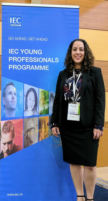 Limor Hochberg standing before IEC conference sign