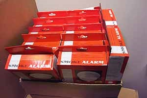 Box of counterfeit smoke alarms. Boxes are orange with the words smoke alarms across the top of the box.