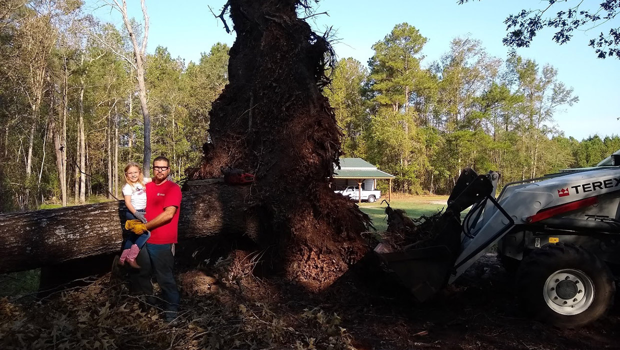 Jeremy Tyndall and his daughter pose before Hurricane Florence debris