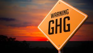 Greenhouse gas warning road sign on sunset sky background