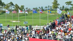 ULIC crowd watches golf event with flags flying in the background.