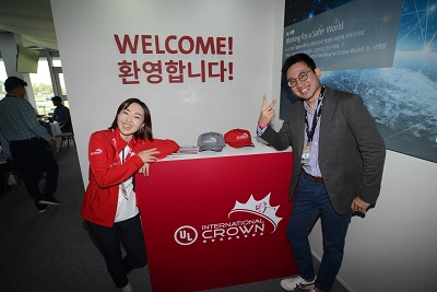 UL Fan Expo visitors greeted by smiling volunteers and a big welcome sign in English and Korean. The volunteers, a man in a grey jacket and a woman in a red jacket smile and pose by a UL International Crown booth.